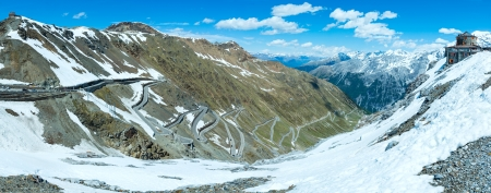 Summer Stelvio pass top with alpine road and snow on slope (Italy) photo