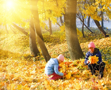 Happy family (mother with daughter) in golden evening maple autumn park and sunshine behind the tree foliage photo