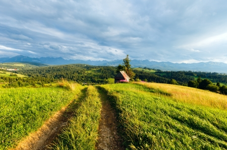 Summer evening mountain village outskirts with country road in front and Tatra range behind (Gliczarow Gorny, Poland) photo