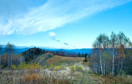 Morning misty autumn mountain landscape with country road on mountainside (Carpathian, Ukraine)