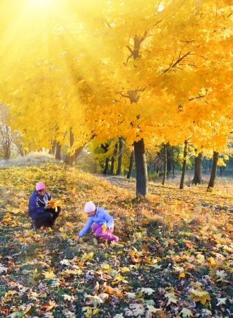 Happy family (mother with daughter) walking in golden maple autumn park and sunshine behind the tree foliage photo