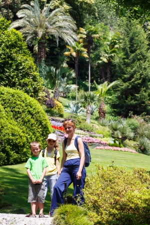 Family in summer city park with blossoming flowerbeds and palm trees photo