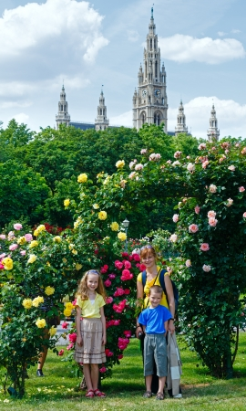 Family near blossoming rose bushes in summer Wien City park. photo