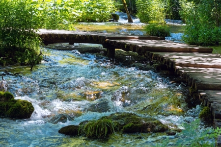 footway: Summer mountain rushing river view with planked footway across the stream in Plitvice Lakes National Park (Croatia)