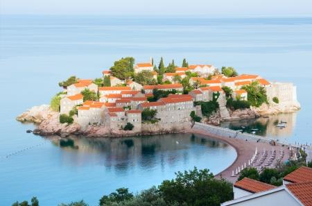 kilometres: The morning view of   Sveti Stefan sea islet with beach and town-hotel(Montenegro, 6 kilometres southeast of Budva)