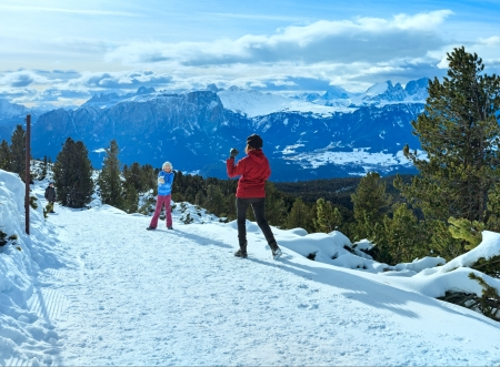 Family  (mother with  two children) plays at snowballs on winter mountain slope. Winter  Dolomiten view from Rittner Horn, Italy. photo