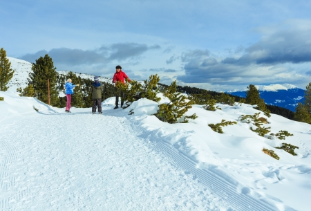 Family  (mother with  two children) plays at snowballs on winter mountain slope photo