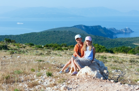 Two children and South cape of Lefkas island (Greece) photo