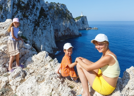 ionian: Family on rocky south cape of Lefkas island and lighthouse (Greece, Ionian Sea) Stock Photo