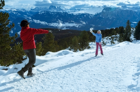 snowball: Family (mother with daughter) plays at snowballs on winter mountain slope