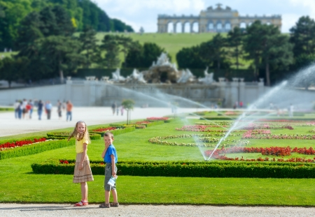 the gloriette: Children in summer park and  Gloriette on hill top (Schonbrunn Palace Garden, Vienna, Austria). All another people is unrecognizable