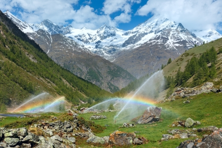 Rainbows in irrigation water spouts in Summer Alps mountain  (Switzerland, near Zermatt) photo