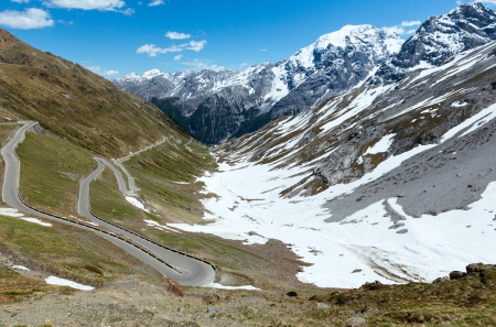 Summer Stelvio Pass with snow on mountainside and serpentine road (Italy) photo