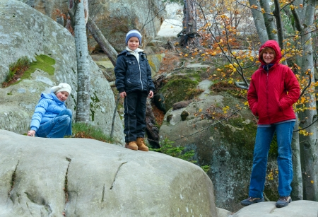 Family in autumn forest with large lofty stones (