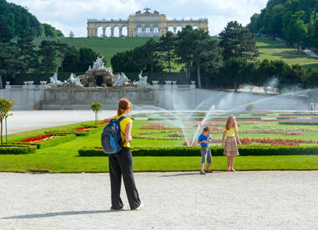 schonbrunn palace: Family (mother with children)  in summer park and  Gloriette on hill top (Schonbrunn Palace Garden, Vienna, Austria). All another people are unrecognizable