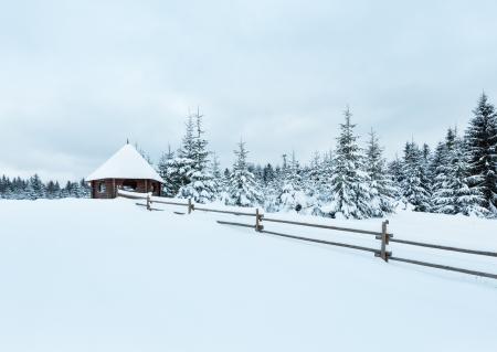 tuinhuis: Houten zomerhuis op de winter heuveltop en sparrenbos achter. Bewolkte dag. Stockfoto