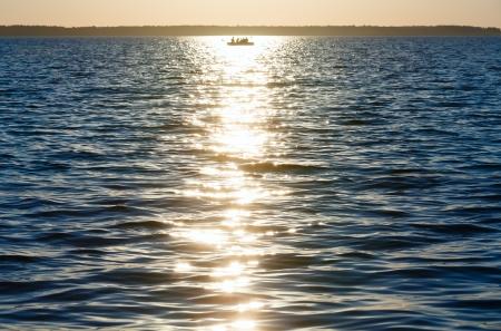 sun track: Sunset, sun track and fishing boat on summer lake surface.