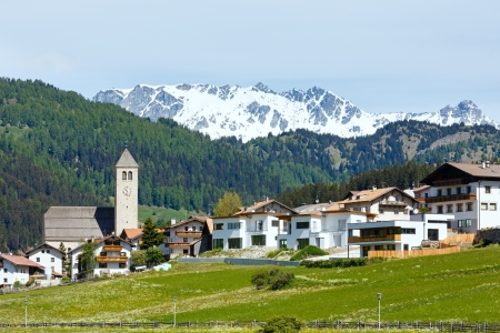 dandelion snow: Summer Alpine mountain village view with grassy meadow (Italy)
