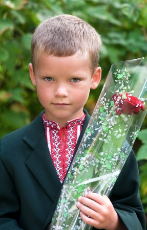 Outdoor portrait of nice little boy before his first visit to the school (with some peel off sunburnt skin on nose) photo