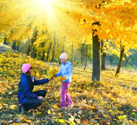 Happy family (mother with daughter) walking in golden maple sunshiny autumn park photo