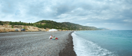 Family on summer beach in Crimea, Ukraine. Black See cloudy panorama. photo