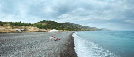 Family on summer beach in Crimea, Ukraine. Black See cloudy panorama. photo