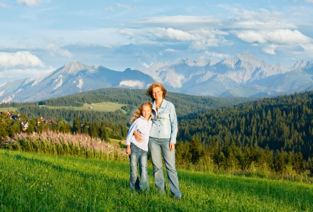Mother with daughter on summer hill and Tatra range behind (Gliczarow Gorny, Poland) photo