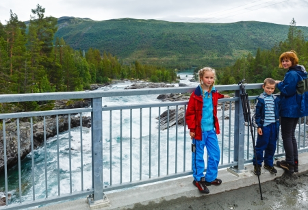 norge: Mother with children on bridge near mountain river waterfalls(Ottafossen, Norge )