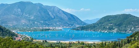 sailer: Many sailing vessels in bay. Hazy summer Lefkada coast panorama (Nydri, Greece, Ionian Sea). Stock Photo