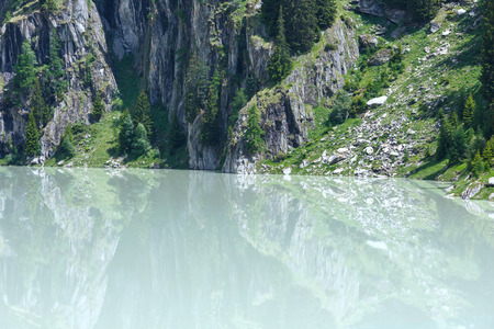 turbid: Lake with turbid water formed the dam. Summer mountain landscape (Alps, Switzerland)