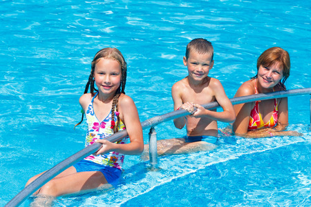 Mother with her children in the summer outdoor pool  photo