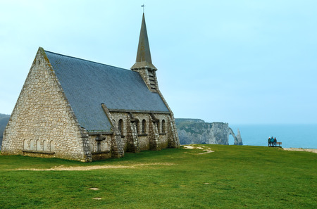 garde: Chapel of Notre-Dame de la Garde (Etretat, Normandy, France) and family on bench. Spring view.
