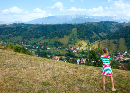 Bran village summer view (near Brasov, Romania) and girl on slope. photo