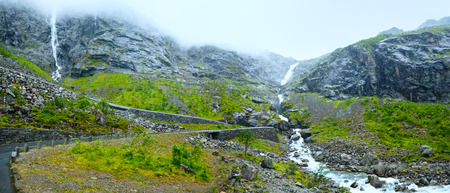 Summer mountain cloudy view with waterfall on Trollstigen (The troll steps) slope (Norway). photo
