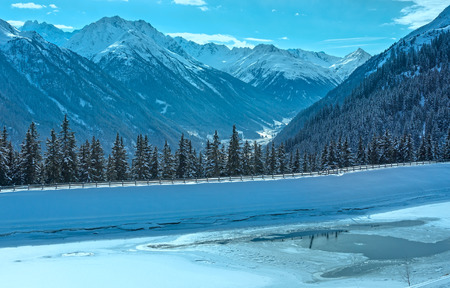 thawing: Winter mountain and thawing lake. Kappl ski region in the Tyrolean mountains, Austria.