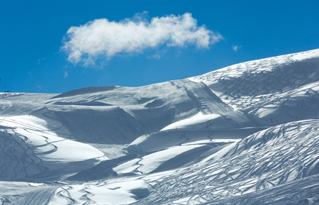 freaked: Hillside freaked ski tracks and lonely cloud in the blue sky. Winter Austria.