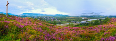 foothills: Summer misty morning country foothills panorama with heather flowers and wooden cross (Lviv Oblast, Ukraine) .