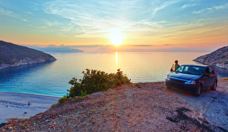 Sea zonsondergang van Myrtos Beach en vrouw in de buurt van de auto (Griekenland, Kefalonia, Ionische Zee). Stockfoto