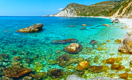 recognize: Petani Beach summer view with big stones in water (Kefalonia, Greece). All people are not recognize. Stock Photo