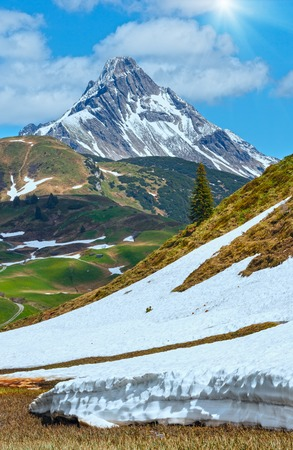 thawing: Summer mountain view to Biberkopf mount, snow thawing meadow, and sunshine in blue sky (Warth, Vorarlberg, Austria).