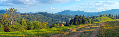 earth road: Mountain evening panorama view with earth road, haystackes and country estate (Carpathian Mts, Ukraine).