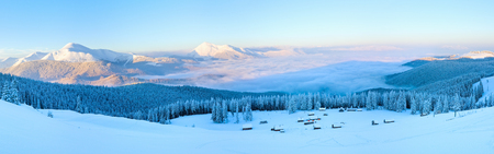 sheds: Morning winter calm mountain panorama with sheds group and mount ridge behind (Carpathian Mountains, Ukraine). Stock Photo