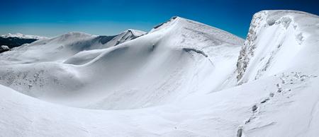 overhang: Winter mountains ridge with overhang snow caps on blue sky background (Ukraine, Carpathian , Svydovets Range, Blyznycja Mount). Stock Photo