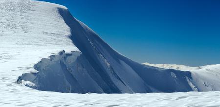 overhang: Winter mountains ridge with overhang snow caps on blue sky background (Ukraine, Carpathian, Svydovets Range, Blyznycja Mount).
