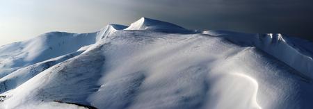 Snow-covered mountain ridge in first daybreak sun rays pastel illumination - day-to-night transition (Ukraine, Carpathian Mountains, Svydovets Range, Blyznytsja Mount).