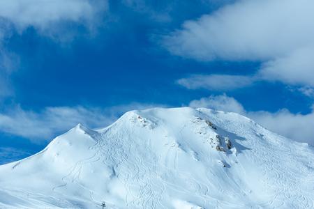 undulate: Hillside undulate ski tracks and clouds in the blue sky. Winter Austria. Stock Photo