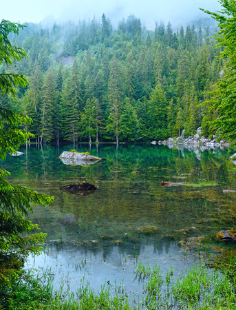 Small mountain forest lake in Franch Alps (misty summer morning). Stock Photo