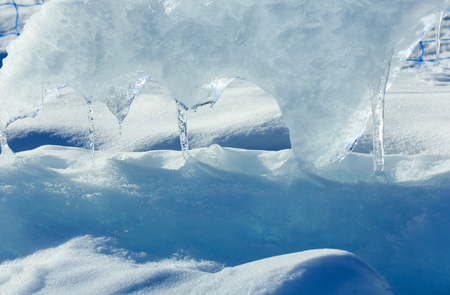 glacial: Melting glacial block of ice with icicles closeup. Stock Photo