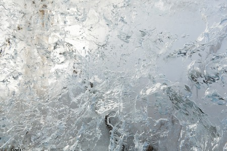 interspersed: Glacial transparent block of ice (close up) with interesting drawings and patterns. Background.