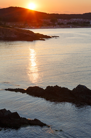 sun track: Sunset sea rocky coast view with sun track on water surface and town beach. Stock Photo